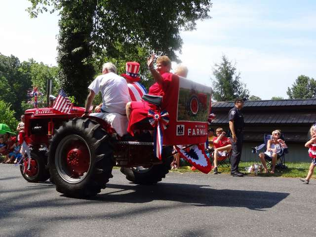 A large farm tractor with an American flag and two riders drives by slowly in a small town parade.