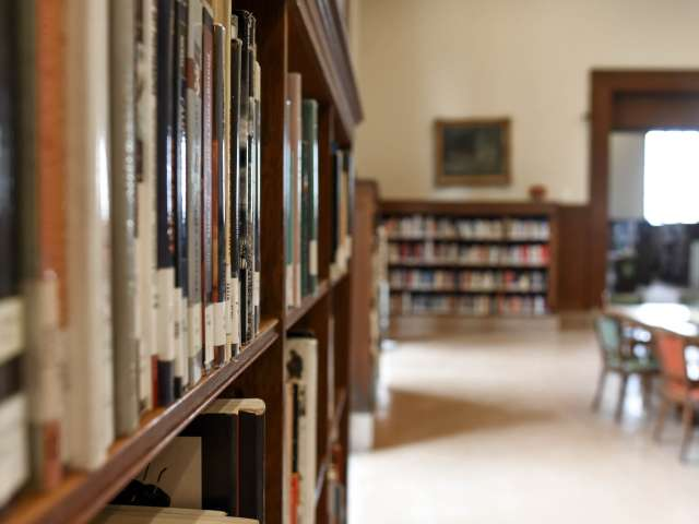 The interior of a small school library, with a close-up of books on the shelf and desks and chairs in the background.
