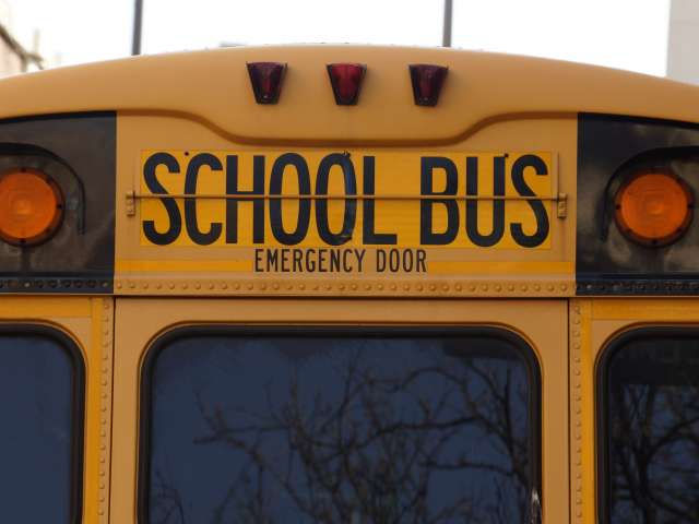 The back of a bright yellow school bus with orange lights, windows, and a door.