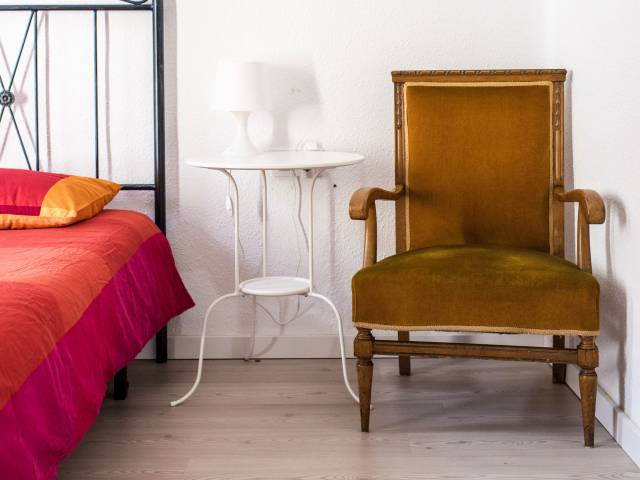 A gold, velvet-covered chair rests next to a bed with a red coverlet.