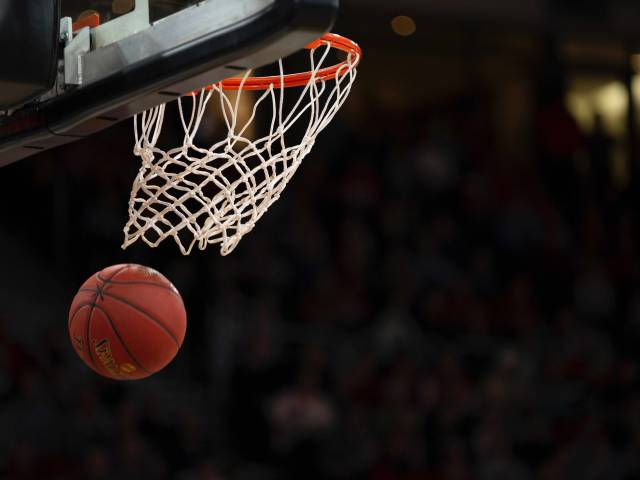 A basketball swooshes through a hoop on a darkly lit basketball court.