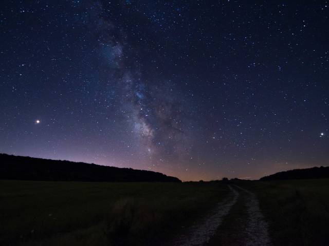 A beautiful, clear night sky with millions of stars over top of a rural field.
