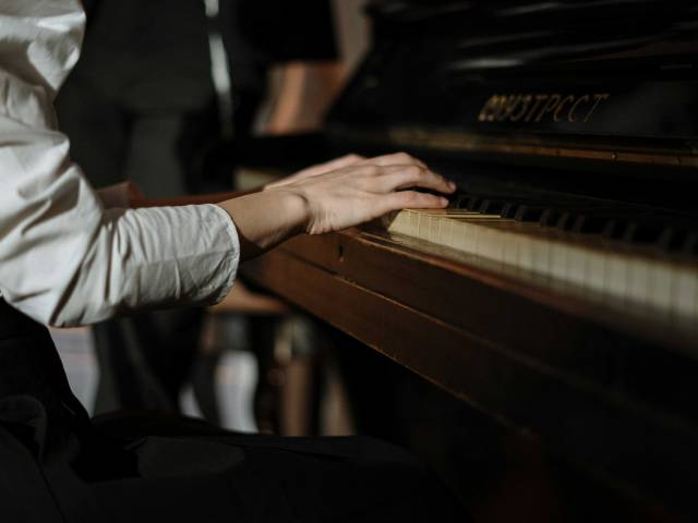 A woman with a white shirt sits at an old piano and plays.