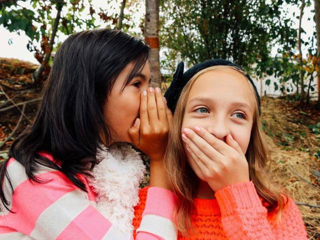 Two young girls in an outdoor setting whisper to each other and laugh.