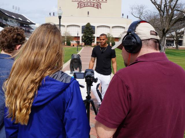 Three students, carrying video recording equipment, interview a young athlete on the campus of a college.