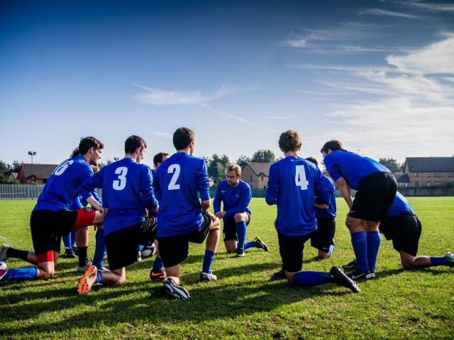 A group of soccer players with blue jerseys kneel on the field in a huddle.