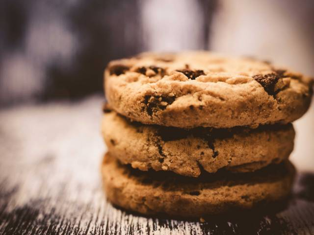 A stack of three delicious chocolate chip cookies on a wooden table.