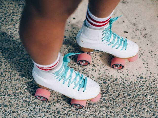 A person wears a pair of white roller skates with pink wheels and teal-blue laces.