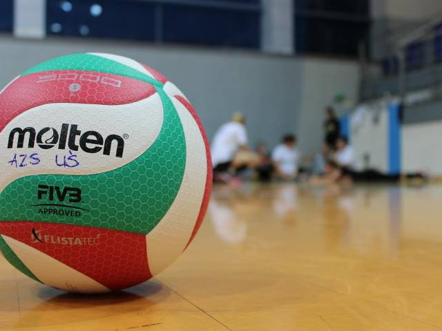 A white, green, and red volleyball sits on a shiny volleyball court.