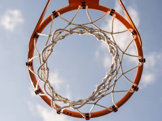 A basketball hoop as seen from the ground up on a sunny day.