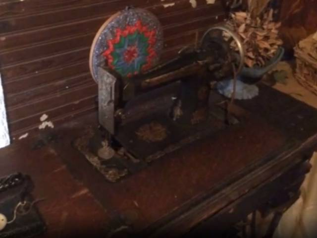 View of a vintage sewing machine in a log-cabin setting.