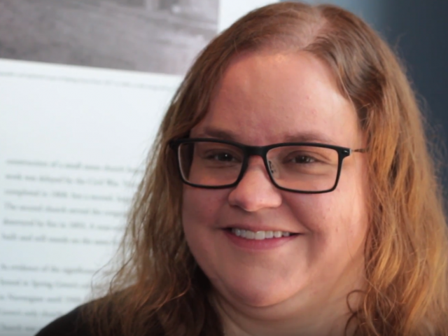 With shoulder-length red hair and black-rimmed glasses, Sarah Schroeder smiles at the camera.