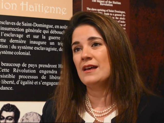 A woman with brown hair and wearing a dark jacket and pearls sits in front of a museum panel and talks to an interviewer.
