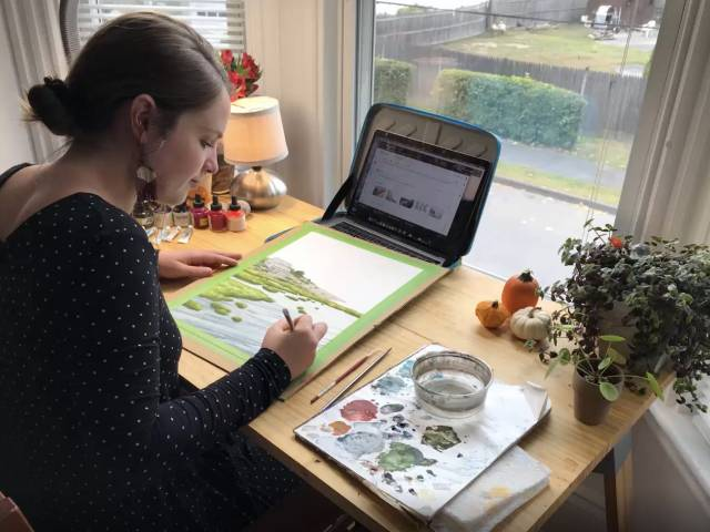 Jill sits at a desk in front of a window with an open computer, a piece of paper, and set of paints.