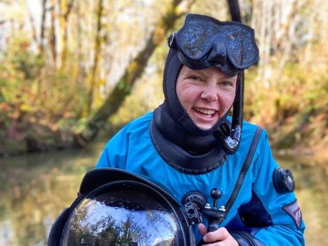 A woman wearing a blue dive suit and holding an underwater camera sits by a lake.