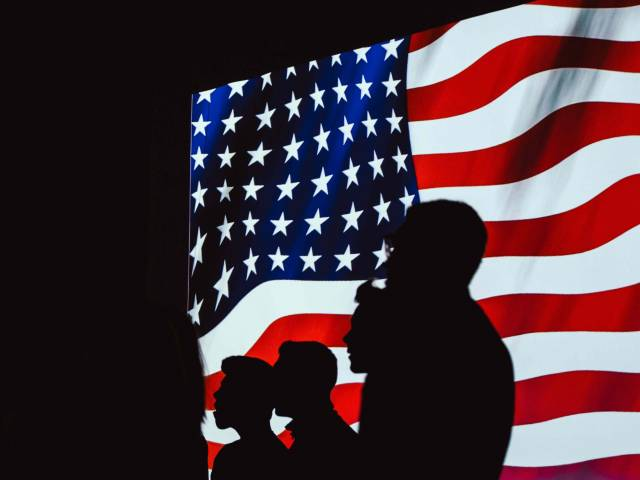 A group of people stand in shadow in front of a bright American flag.