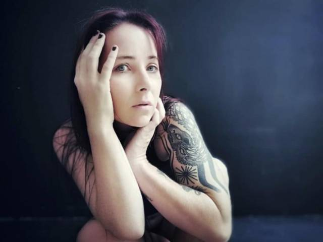Polly has dark hair and tattoos on her arms. She puts her hands on her face in the photo.