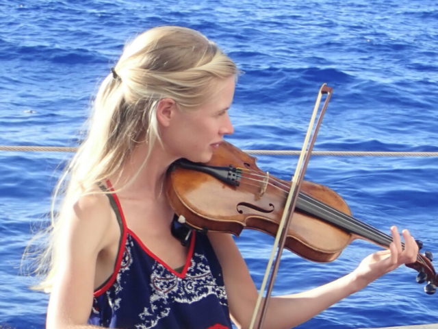 With long blonde hair, Sophie Davis plays a violin beside the water.