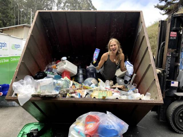 With long blonde hair, Yustina rummages through a large dumpster and pulls out trash.