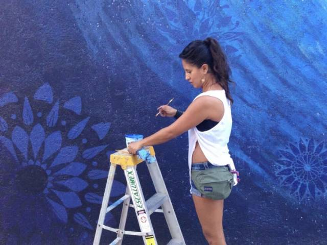 Adriana wears a white tank top and shorts as she stands on a ladder to paint a mural of water.