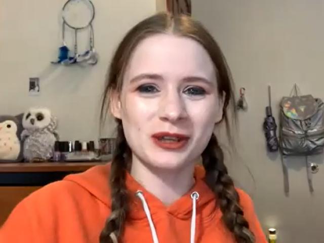 Amber Dukeman wears braids in her hair and a bright orange hooded sweatshirt.