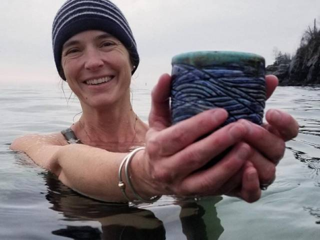 A woman with a swim cap on raises her hands out of the water and holds a cup in her hands.