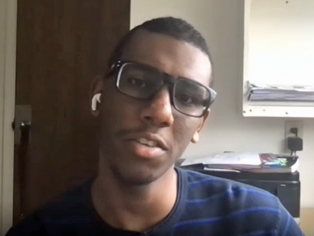 Amir has short cropped hair, a blue t-shirt, and glasses. He sits in a dorm room.