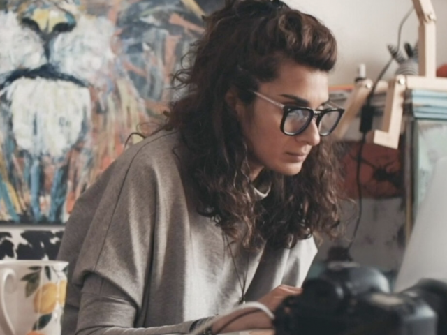Asher has shoulder-length brown hair and thick reading glasses on. She sits at a desk with painting supplies.