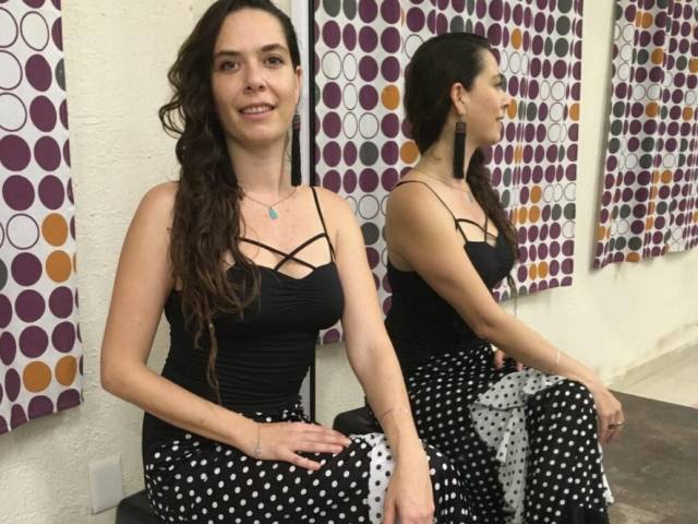 A woman with long, black hair and a black tank top sits in a dance studio.