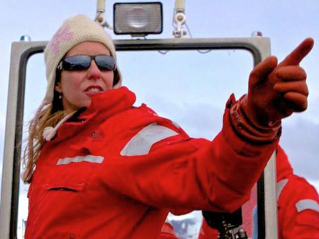 A woman points out to the water as she wears a bright, red coat, sunglasses, and warm, woolen cap.