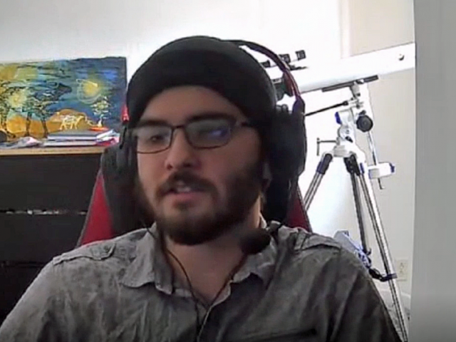 Dylan has a black knit cap on and headphones. He sits in front of a telescope and colorful painting.