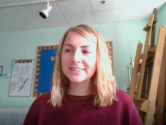 Kacie has shoulder-length blonde hair and wears a bright, red sweater. She sits in a classroom environment.