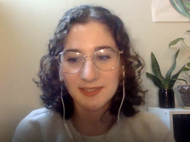 Sabrina has curly, brown hair, white headphones on, and clear-rimmed eye glasses.