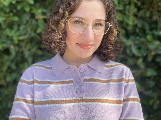 Sabrina has short, brown curly hair, eye glasses, and a purple and brown striped sweater on. She stands in front of greenery outside.