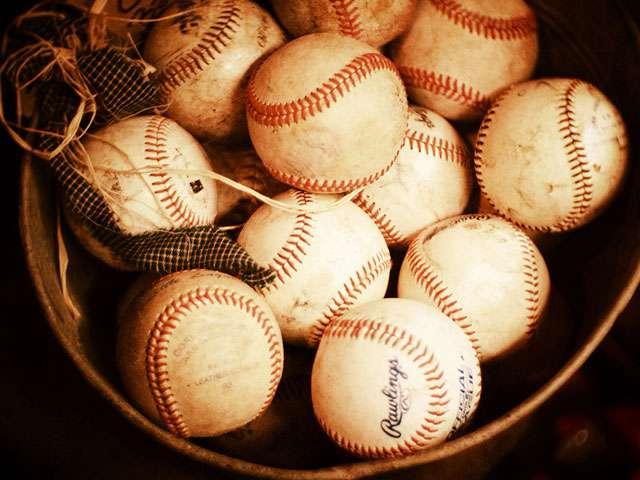 A basket full of vintage baseballs.