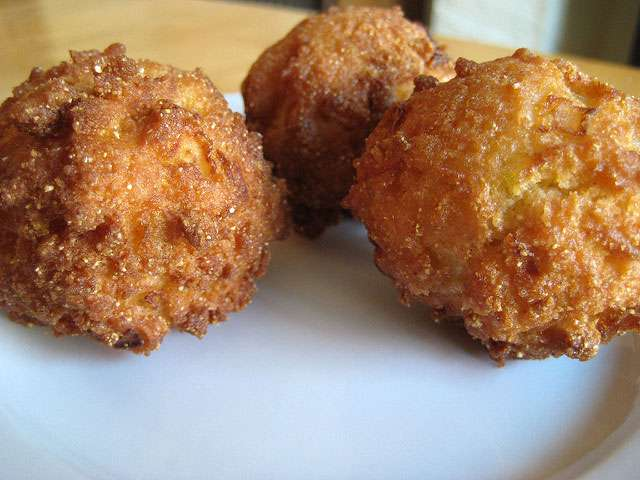 Deep-fried hush puppies sit on a plate.