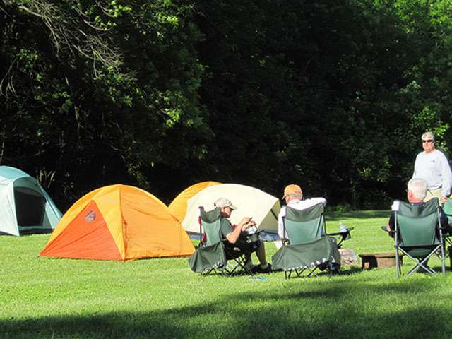 A group of campers sit outside of their colorful tents.