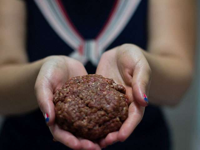 A woman holds a ball of ground beef.