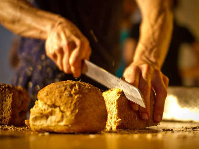 A old woman's hands slice bread.