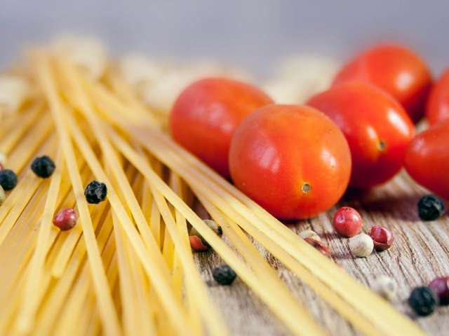 Uncooked spaghetti noodles, pepper corns and grape tomatoes on a cutting board. Pixabay stock photo.