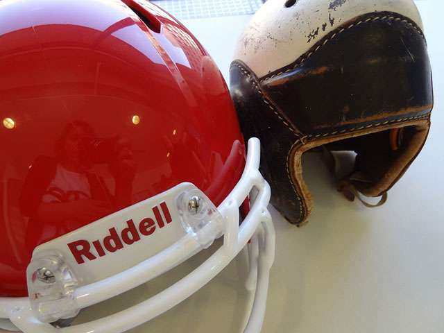 A bright red, modern football helmet positioned next to an antique leather football helmet. Photo by Heather Shelton