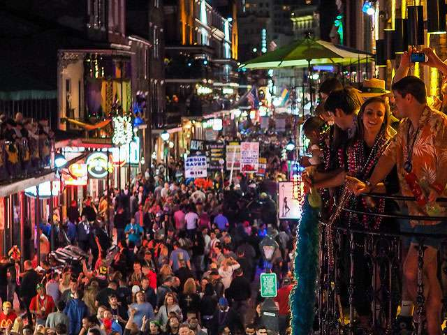 A crowd of Mardi Gras revelers, some standing on balconies.
