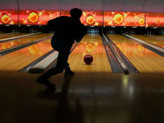The back of a person releasing a ball at a bowling alley.