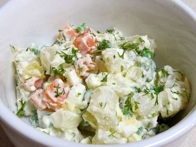 A white bowl filled with a creamy potato salad dish.