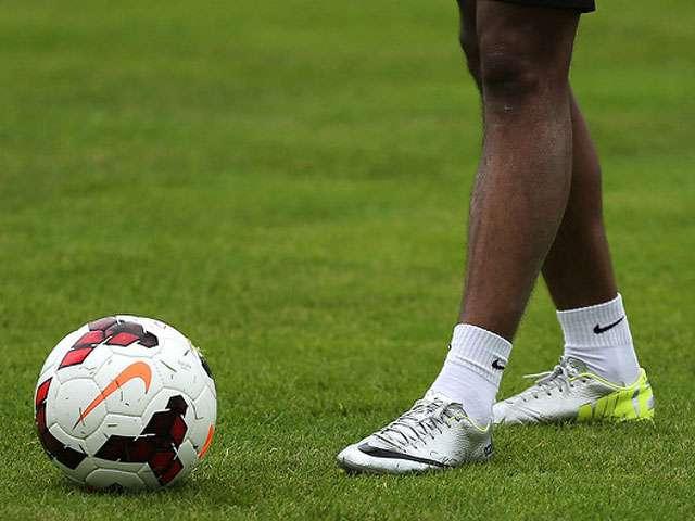 A detail of a man's legs as he approaches a soccer ball.