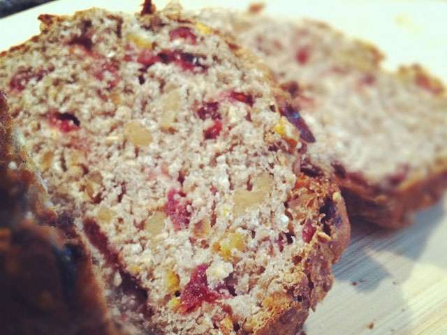 An image of dense bread or cake with nuts and various berries.
