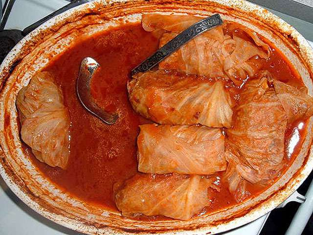 A soupy plate with cooked cabbage rolls.