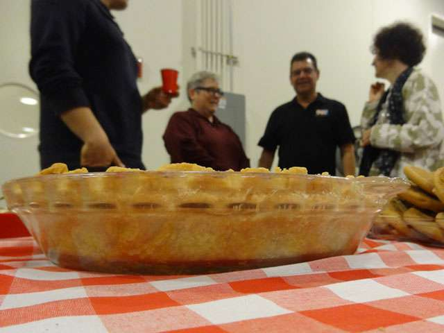 People stand around a table on which rests an apple pie.