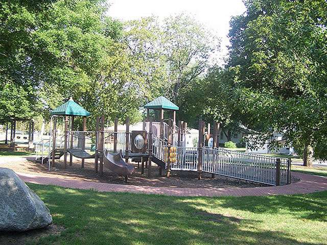 A summertime view of a wooden playground with slides.