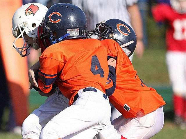 Pee-wee football players run down in the field in orange jerseys.